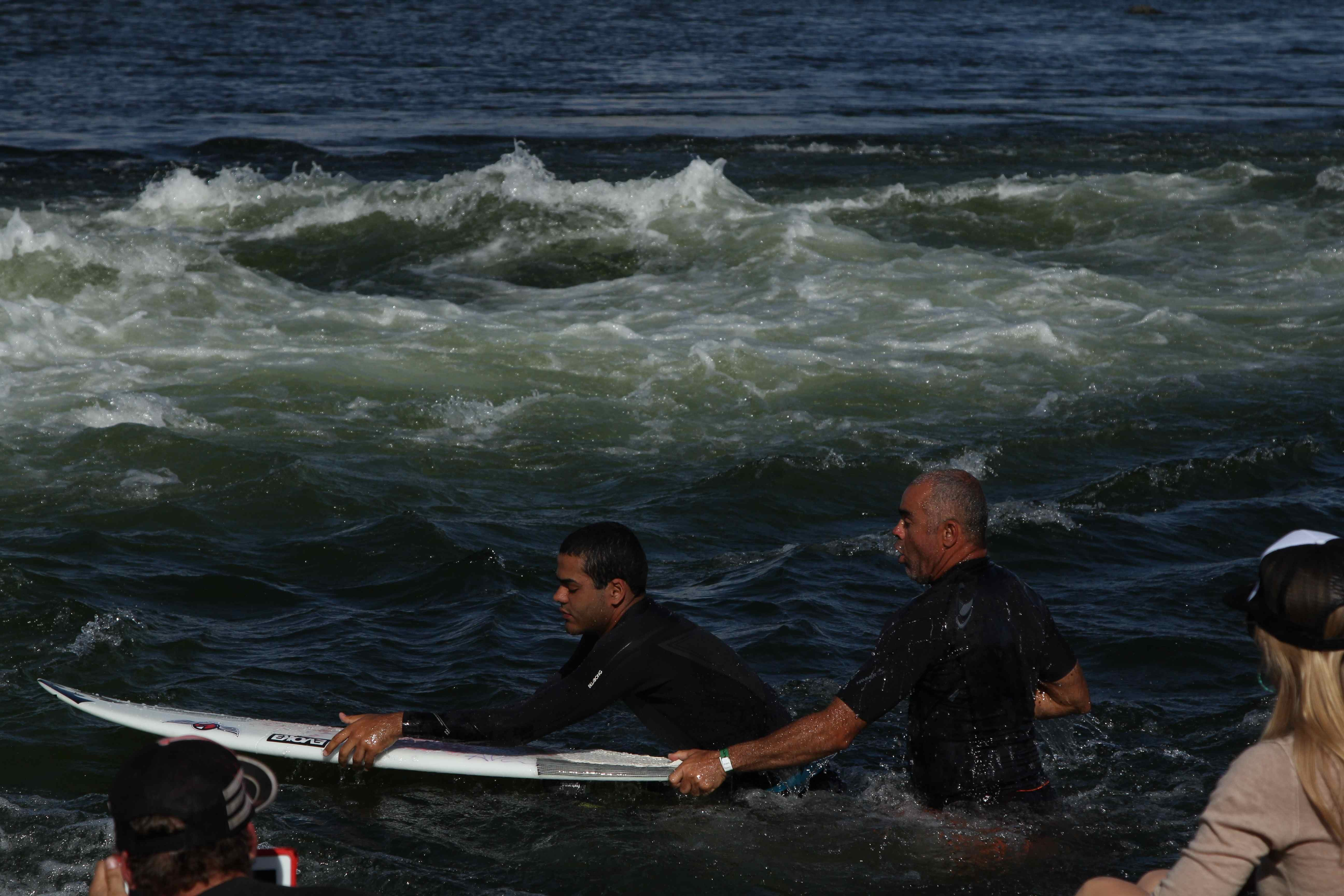 Derek prepares to surf with the help of his dad as KWP founder Kristina Pickard watches on