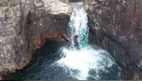 English paddler Thadeus Hayes, running a waterfall in his kayak on the Etive in Scotland
