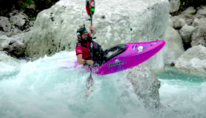 kayaker paddles the soca river in slovenia.